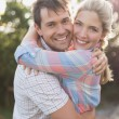 Portrait of a smiling couple embracing in park — Stockfoto