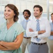 Business group with arms crossed in office — Stock Photo #42585343