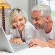 Happy mature couple using laptop in bed — Stock Photo