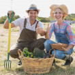 Couple with vegetables gesturing thumbs up in field — Stock Photo