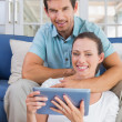 Happy couple using digital tablet on couch — Stock Photo