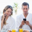 Couple using mobile phones while having breakfast — Stock Photo #42586197