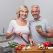 Happy mature couple preparing food together in kitchen — Stock Photo #42586663