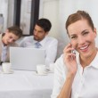 Businesswoman using mobile phone with colleagues at office desk — Stock Photo #42586777
