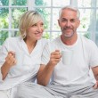 Smiling mature couple with coffee cups sitting on bed — Stock Photo #42586895