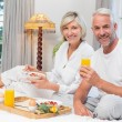 Mature couple having breakfast in bed — Stock Photo #42587149