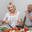 Mature man with wine glass and woman chopping vegetables in kitchen — Stock Photo #42587511