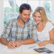 Couple with financial documents and calculator at home — Stock Photo