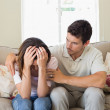 Man consoling a sad woman in living room — Stock Photo #42589705