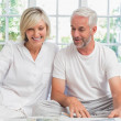 Smiling mature couple sitting on bed at home — Stock Photo #42589797