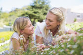 Mother and daughter lying in park — Stock Photo