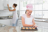 Girl looking at freshly prepared cookies with mother in kitchen — Stock Photo