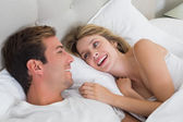 Relaxed young couple resting in bed — Stock Photo