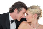 Smiling bride and groom with head to head — Stock Photo