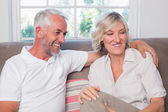 Happy relaxed mature couple sitting on sofa — Stock Photo