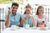 Веселые друзья, чтение текстового сообщения в кафе — Стоковое фото