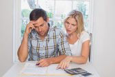 Worried couple with financial documents and calculator — Stock Photo