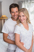 Smiling couple standing together at home — Stock Photo