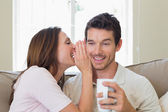 Woman whispering secret into a happy mans ear in living room — Stock Photo