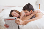 Couple reading newspaper together in bed — Stock Photo