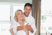 Loving man embracing woman from behind at home — Stock Photo
