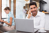 Happy man using laptop and mobile phone in coffee shop — Stock Photo