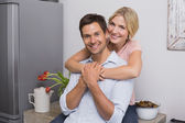 Smiling woman embracing man from behind at home — Stock Photo