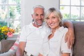 Smiling mature couple sitting on sofa in living room — Stock Photo