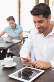 Man text messaging in coffee shop — Stock Photo