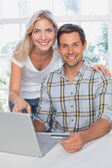 Smiling young couple doing online shopping at home — Stock Photo