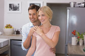 Happy loving couple standing in the kitchen — Stock Photo