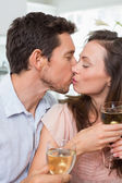 Loving couple with wine glasses kissing at home — Stock Photo