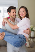 Man carrying woman at home — Stock Photo