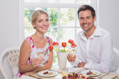 Happy young couple with wine glasses having food — Stock Photo