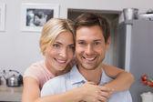 Улыбается женщина, обнимая мужчину сзади в кухне — Стоковое фото