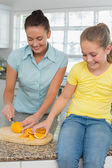 Woman slicing oranges for daughter in kitchen — Stock Photo