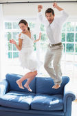 Cheerful young couple jumping on couch — Стоковое фото