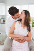 Loving young couple kissing in kitchen — Stock Photo