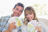 Portrait of a young couple holding fanned out Euro notes — Stock Photo