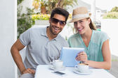 Smiling couple using digital tablet at cafe — Foto de Stock