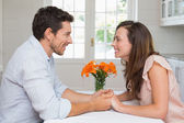 Loving young couple holding hands in kitchen — Stock Photo