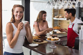 Woman drinking coffee with friend and male barista in coffee shop — Stockfoto