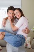 Smiling man carrying woman at home — Stockfoto