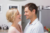 Cariñosa pareja mirando el uno al otro en la cocina — Foto de Stock
