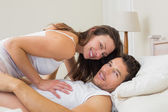 Relaxed couple lying together in bed — Stock Photo