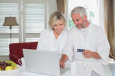 Happy mature couple doing online shopping at home — Stock Photo