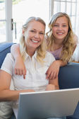 Girl pointing at laptop while mother using it — Stock Photo