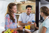 Couple paying bill at coffee shop using card bill — Stock Photo