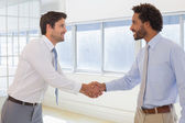 Smiling young businessmen shaking hands in office — Stock Photo