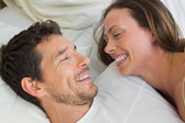Cheerful couple lying together in bed — Stock Photo
